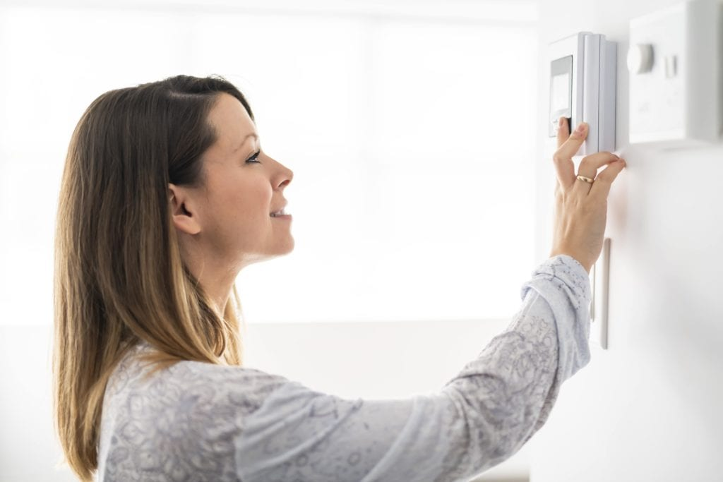 woman adjusting thermostat