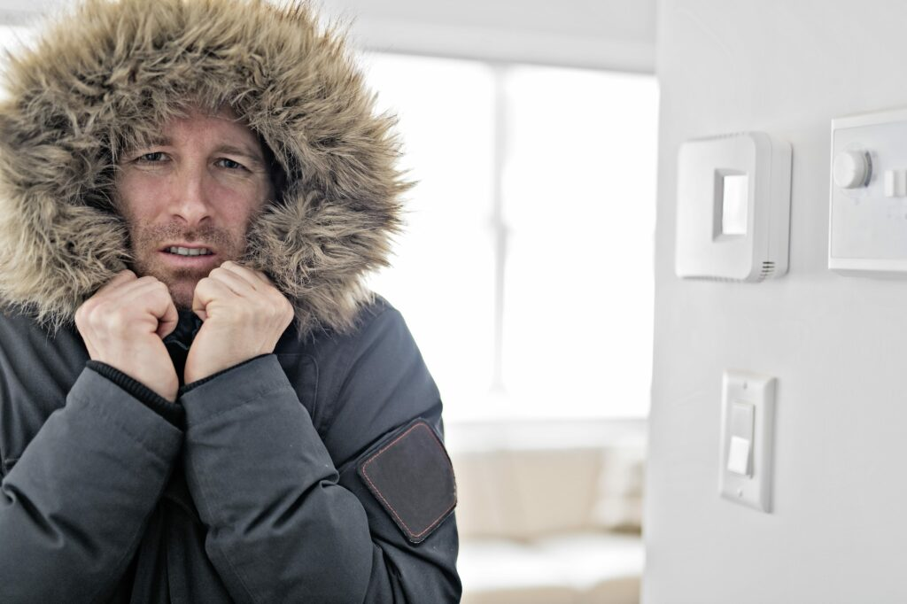man freezing at home due to broken heating system