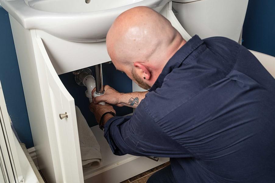 https://www.marklindsayplumbing.com/wp-content/uploads/plumber_fixing_under_sink-1.jpg