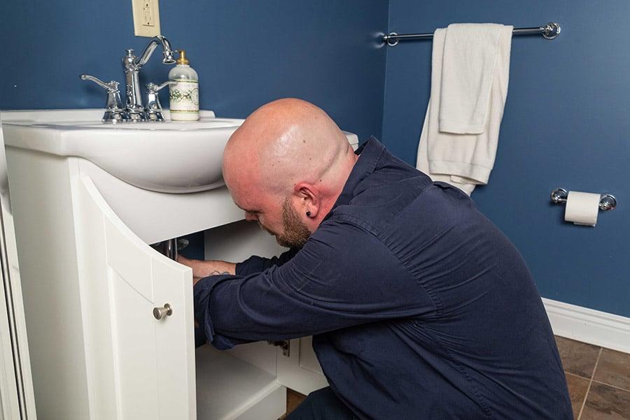 https://www.marklindsayplumbing.com/wp-content/uploads/plumber_fixing_under_sink2.jpg